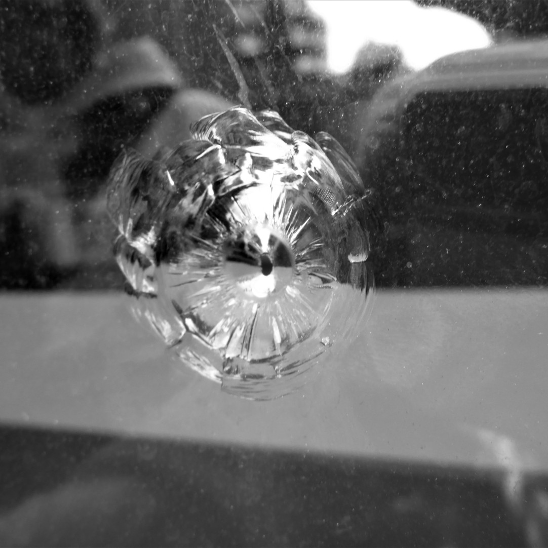 Impact: This chip actually has a small hole at the centre that goes full depth. Some sort of projectile seems to have been fired at the glass from the outside.